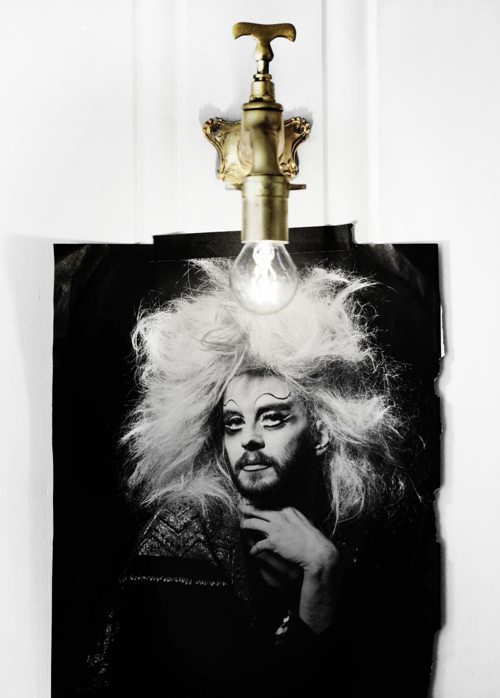 KREATIV KUNSTNERGAVE: Lampen er laget av en gammel messingkran, og er en gave fra kunstnervennen Kjetil Aschim, som lager brukskunst av gjenbruksmaterialer. Bildet på veggen har Ive hentet fra et blad, for henne symboliserer det viktigheten av ikke å ta seg selv så høytidelig.   Foto: Nina Ruud