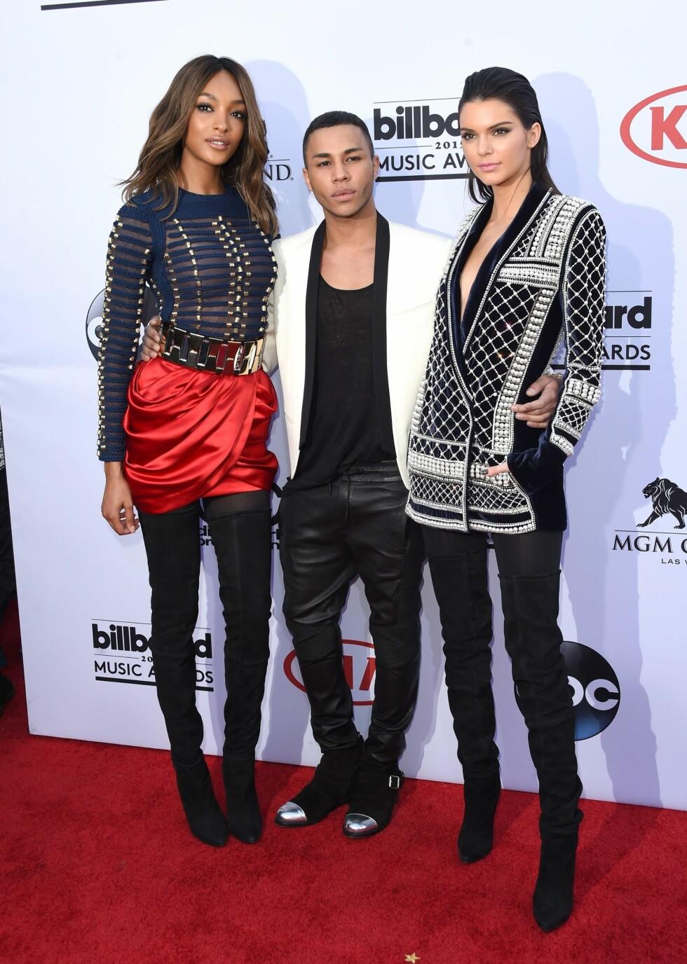 MED SJEFSDESIGNEREN: Her er modellene Jourdan Dunn og Kendall Jenner med Balmains sjefsdesigner Olivier Rousteing på Billboard Music Awards. Begge modellene bar plagg fra H&M-kolleksjonen, som lanseres 5. november.  Foto: Afp