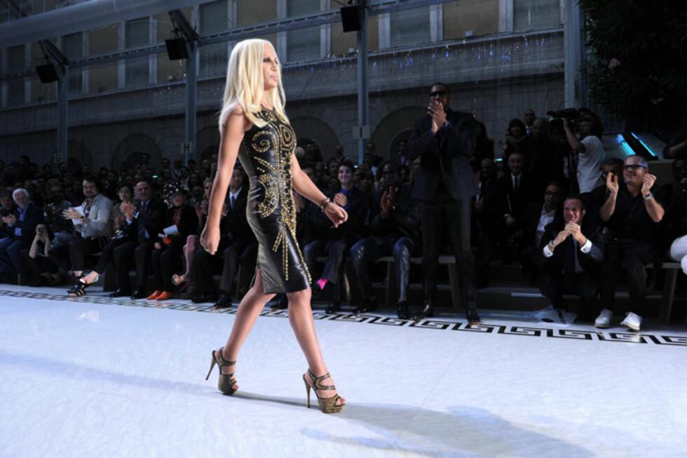 Donatella Versace har på seg en av av kjolene fra Versace for H&M kolleksjonen på visningen av Versaces herre moteshow  i Milan den 20.juni. Foto: Versace for H&M