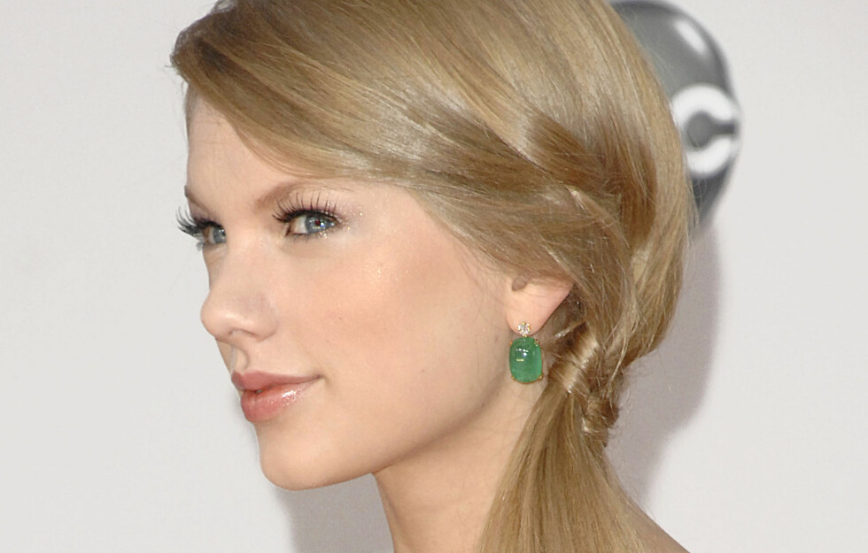ENKELT: Den lille åttetallsfletten som fester sidehestehalen gjør denne frisyren glamorøs og litt annerledes, noe Taylor Swift ser ut til å elske. Foto: All Over Press