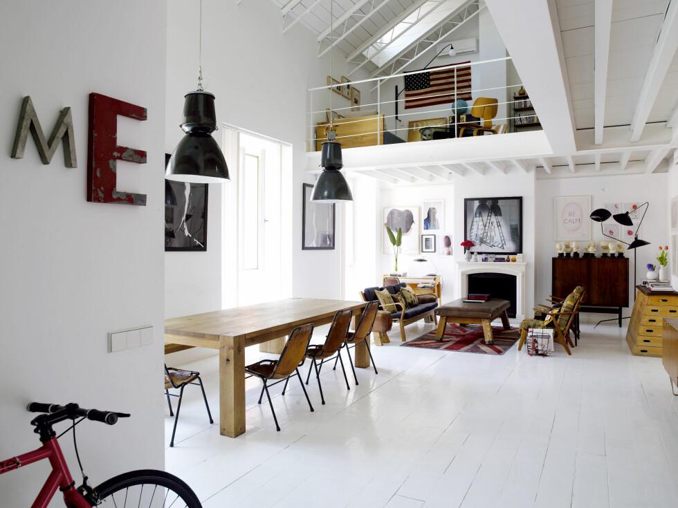 Spisebordet i eik er tysk design fra E15.com. Rundt det står stolene Charlotte Perriand designet i 1972. De industrielle lampene er fra Elteatrodelossuenos.com. Kunst av husets herre. Foto: Richard Powers/IDECOR images