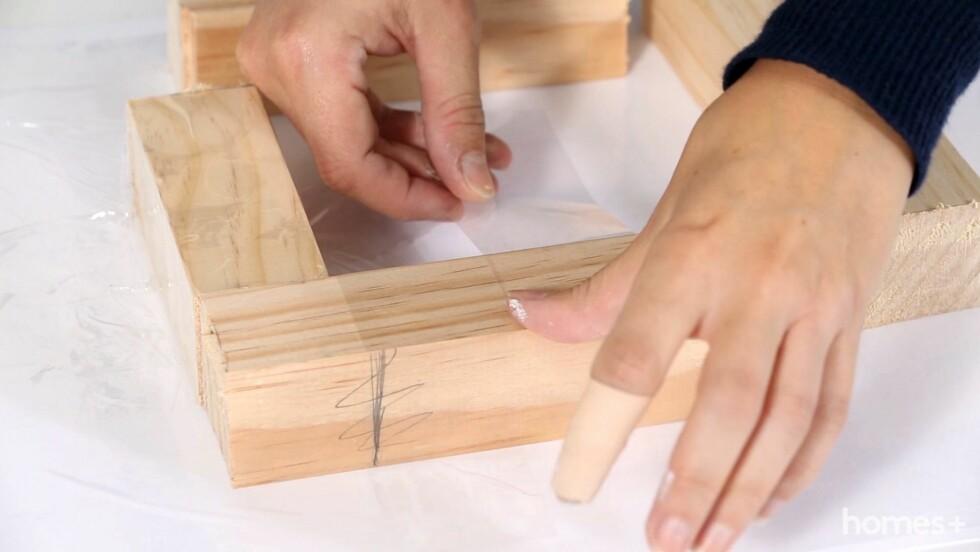 2. Bruk en håndsag til å kappe trevirke i fire like store deler. Du trenger dem til å støpe betongblokken. Fest rammen med tape til pappunderlaget. Dekk hele flaten på innsiden med tape. Foto: Bulls Press - Bauer Media Group