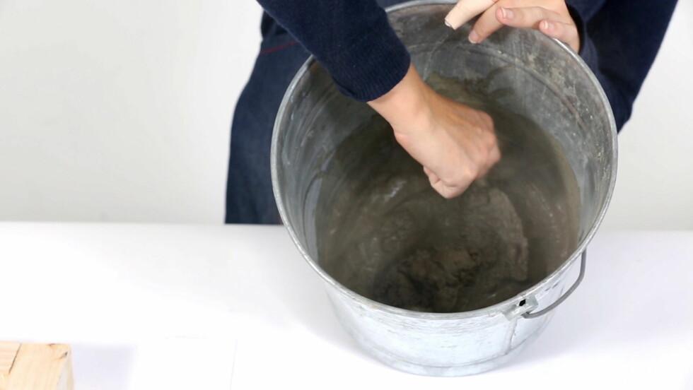 3. Ha betongmiksen i en bøtte og tilsett vann. Bland sammen med en gammel skje til det blir en glatt, jevn masse.  Foto: Bulls Press - Bauer Media Group