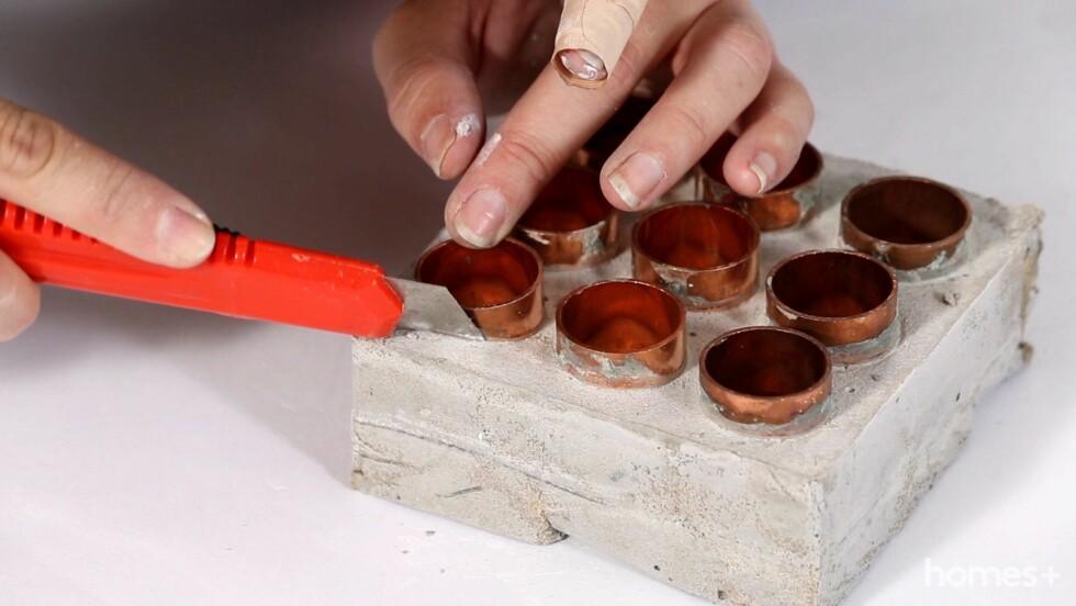 6. Fjern forsiktig tørket betong fra kobberet med en tapetkniv. Nå er stativet ferdig, og du kan sette reagensglass med krydder på plass i kobberkoblingene. Til slutt kan du merke glassene med Dymo-lapper, så får de en kul retro-look. Foto: Bulls Press - Bauer Media Group