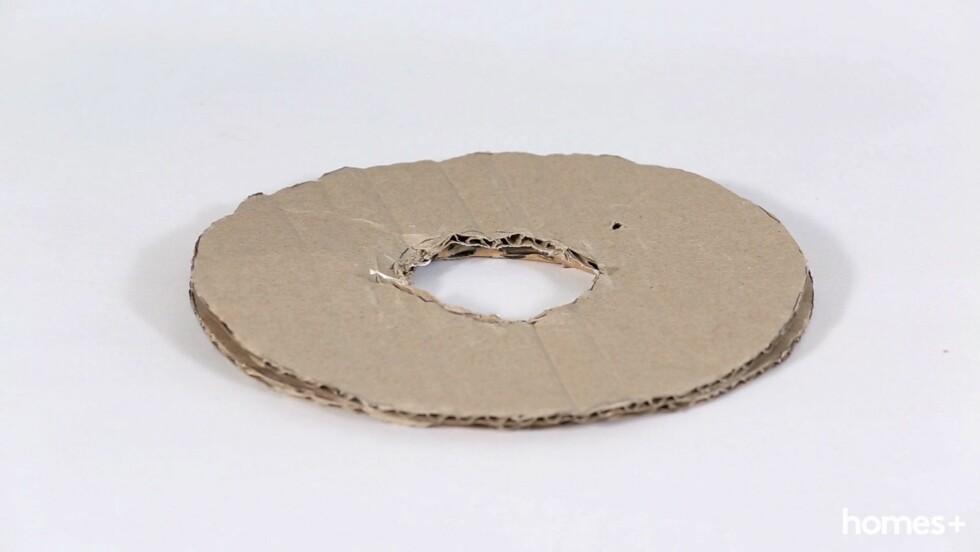 3. Klipp ut den store sirkelen, og klipp så ut den mindre slik at du står igjen med en smultringform. Gjenta prosessen så du har to pappsmultringer. Foto: Bulls Press - Bauer Media Group