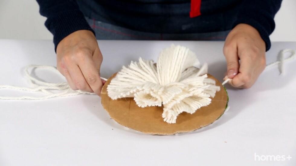 6. Ta en ny lengde garn mellom pappskivene, stram godt til og knytt godt. Dette binder garnet sammen til en pompong. Trekk ut pappskivene. Foto: Bulls Press - Bauer Media Group