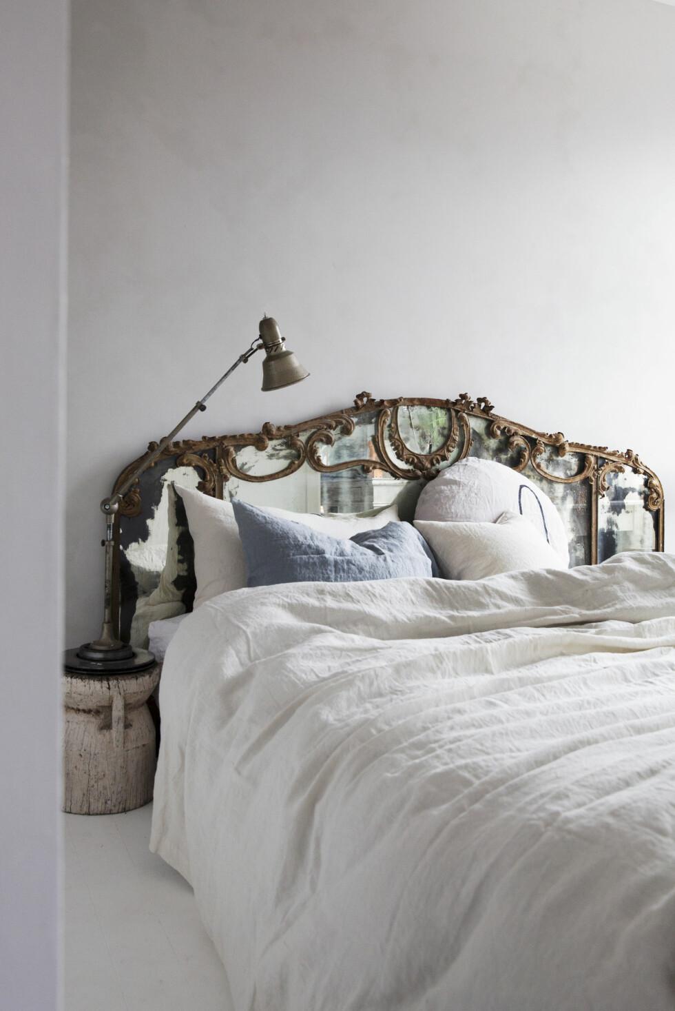 Den vakre, gamle sengegavlen er fra MO Inredning. Linsengetøyet er fra Eske, lampen og stolen fra Fransk bazar og stubben fra Anouska. – Sengegavlen og stubben passer jo egentlig ikke sammen, men nettopp derfor  synes jeg det fungerer så godt, sier Tone.   Foto: Yvonne Wilhelmsen