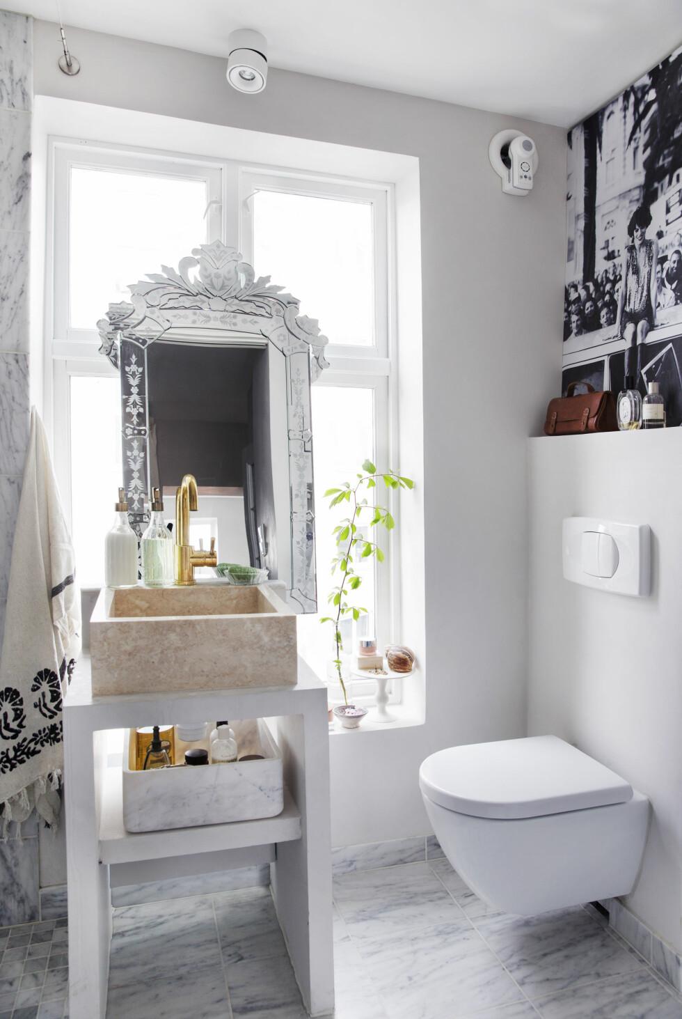 Badet i marmor og messing er fra Flisekompaniet, og ser mye dyrere ut enn det var. Vasken fra Anouska står foran vinduet, utradisjonelt, men fint. Speilet i vinduet har fulgt Tone i mange år.  Foto: Yvonne Wilhelmsen