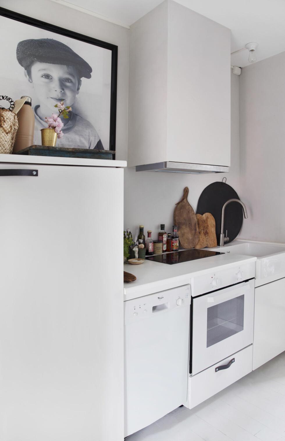 Kjøkkenet er kompakt, men virker større enn det er. Tone synes metallvifter er så kjedelige, så hun fikk kasset inn kjøkkenviften med gipsplater. Skinnhåndtakene på skapdørene er fra BonDep.no. – Skinn er så levende, det blir bare tøffere.  Foto: Yvonne Wilhelmsen