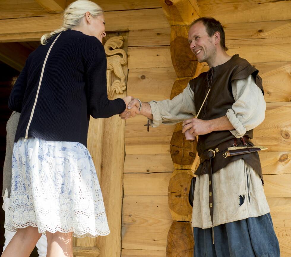 HÅNDTRYKK: Mette-Marit ble takket av Kai Rune Johansen etter å ha åpnet Gjesteloftet på Stiklestad. Strikkegenseren hennes hadde en original detalj i form av lys glidelås på ryggen.   Foto: NTB scanpix