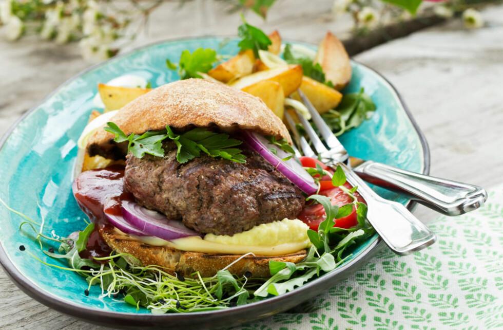 HAMBURGER: Grillede burgere er en sommerklassiker. Prøv denne varianten med løk, dijonsennep og spisskummen. Ovnsbakte potetbåter smaker godt til burgeren. Foto: All Over Press