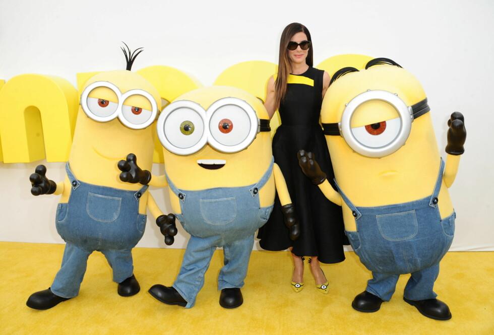 GULE HJELPERE: Sandra poserte med tre Minions på løperen, som for anledningen var gul istedenfor rød.  Foto: Ap