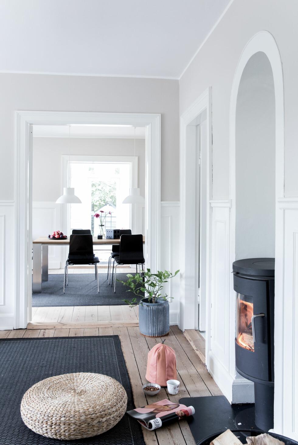 BRUK LYSET: Stuen, spisestuen og hagestuen ligger rett etter hverandre så man kan se hvordan lyset faller inn i alle rommene. Den lille puffen fra IKEA er perfekt å sette foran vedovnen en kjølig ettermiddag. Foto: Pernille Kaalund