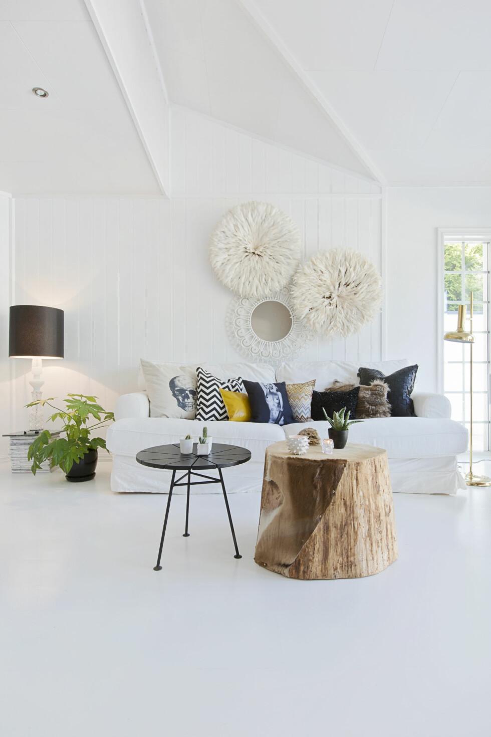 LYST OG LUFTIG: Den myke, hvite sofaen har fulgt paret lenge og er deilig å sitte i. Putene skaper kontraster og spenning med ulike materialer og trykk. Stuebordet har Linn laget selv, og juju-hattene er fra Linns tid med import fra Sør-Afrika. Lampen med svart skjerm er fra Design by us (kr 7900, zanz.no). Foto: Jorunn Tharaldsen
