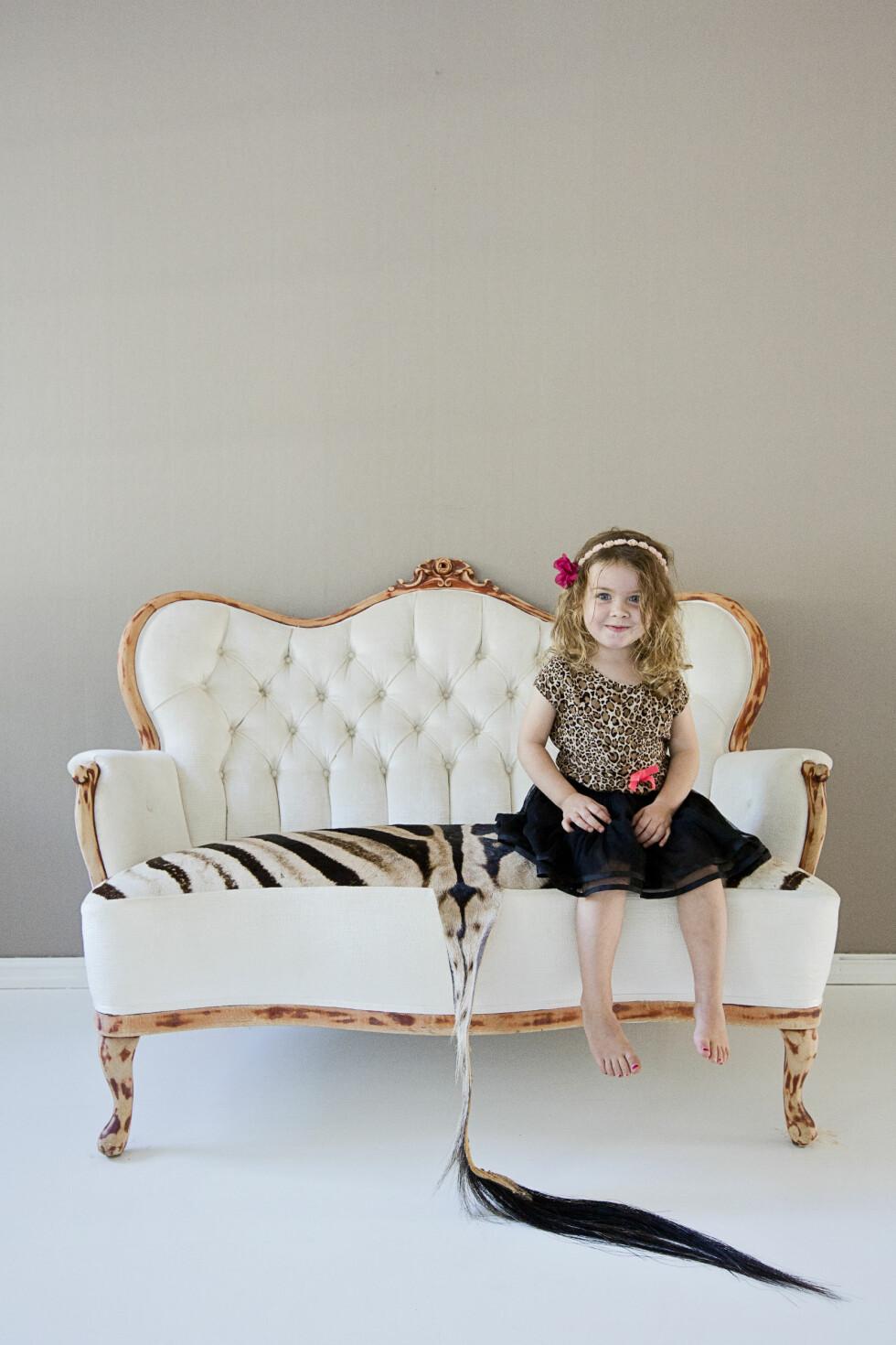 FAVORITT: Datteren Imka Elvira trives i den gamle rokokkosofaen Linn kjøpte brukt for flere år siden, og som hun fikk trukket om av en møbeltapetserer. Sebraskinnet kjøpte Linn på en av sine mange turer i Sør-Afrika.   Foto: Jorunn Tharaldsen
