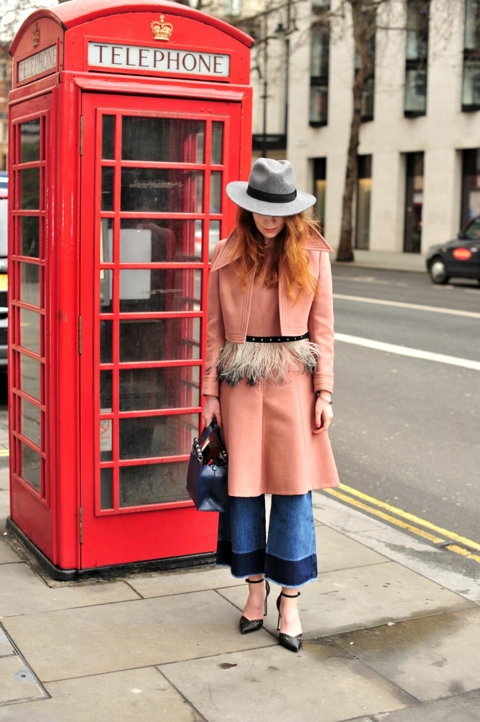 Moteblogger Christie Stankeviciute stylet buksene med en pastellfarget kåpe og høye hæler under moteuken i London.  Foto: Scanpix