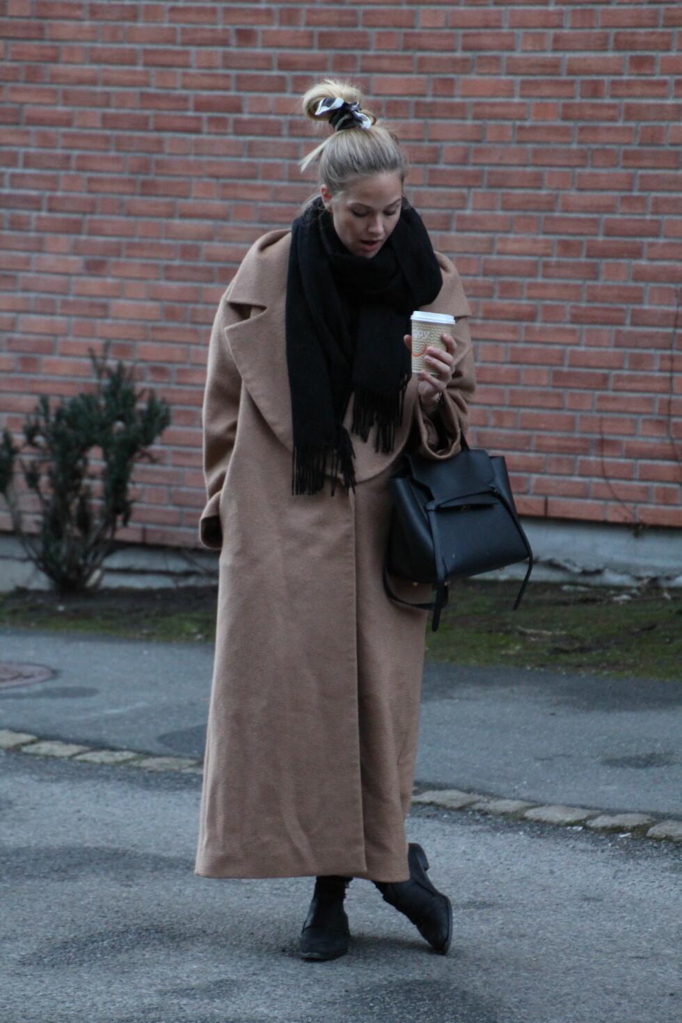 VINTERSTIL: Maria kler seg i en overdimensjonert, kamelfarget frakk som hun styler med svart tilbehør og setter kronen på verket med et tørkle i håret.  Foto: Mariaskappel.no