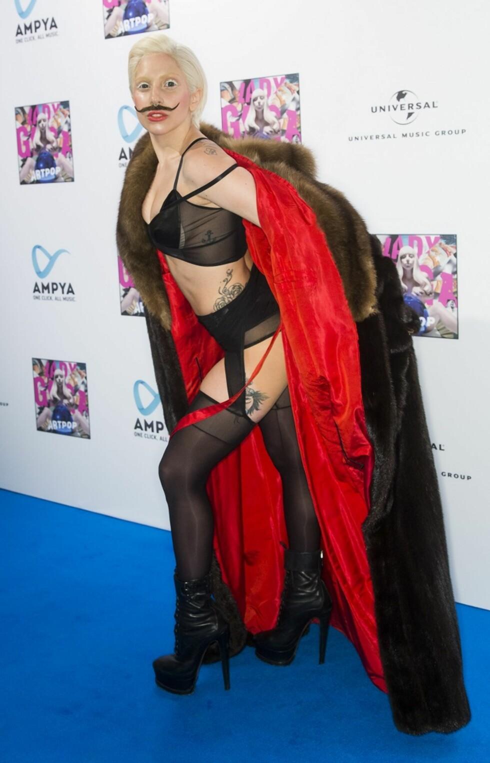 I Berlin dukket i 2013 Lady Gaga opp med den uvanlige kombinasjonen av bart og undertøy.  Foto: All Over