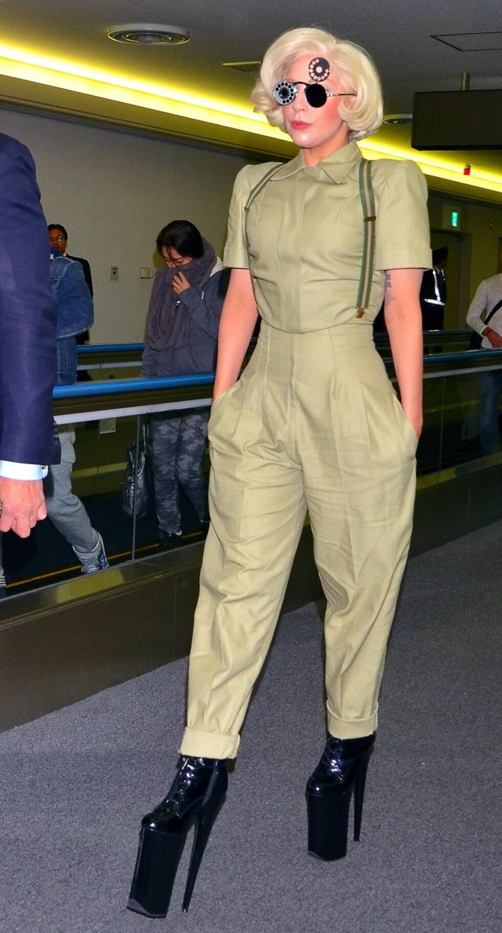 Antrekket var streit nok på flyplassen i Tokyo, men solbrillene og skoene var typisk Gaga anno 2013.  Foto: All Over