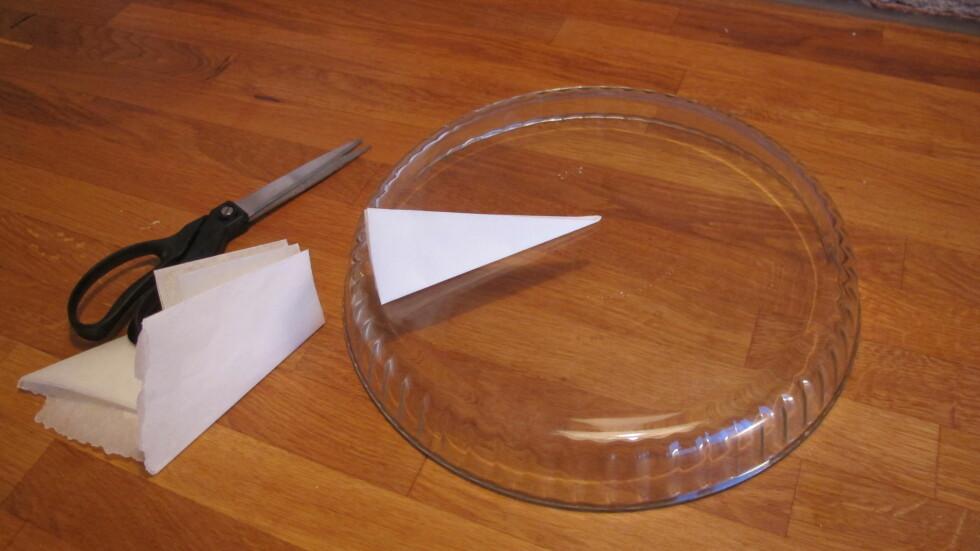 6. Så legger du det sammenbrettede bakepapiret med trekantspissen inn i sentrum av formens bunn, og klipper av ute ved kanten. Foto: Stine Okkelmo