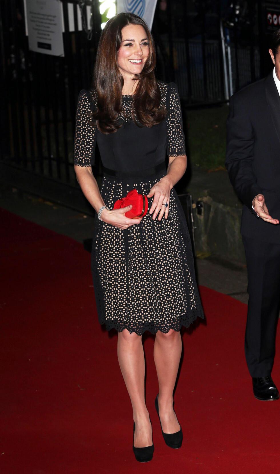 FLATTERENDE LENGDE: Hertuginne Kate i en kjole fra Temperley som stopper rett over kneet. Den røde vesken er signert Alexander MqQueen.  Foto: REX/All Over Press