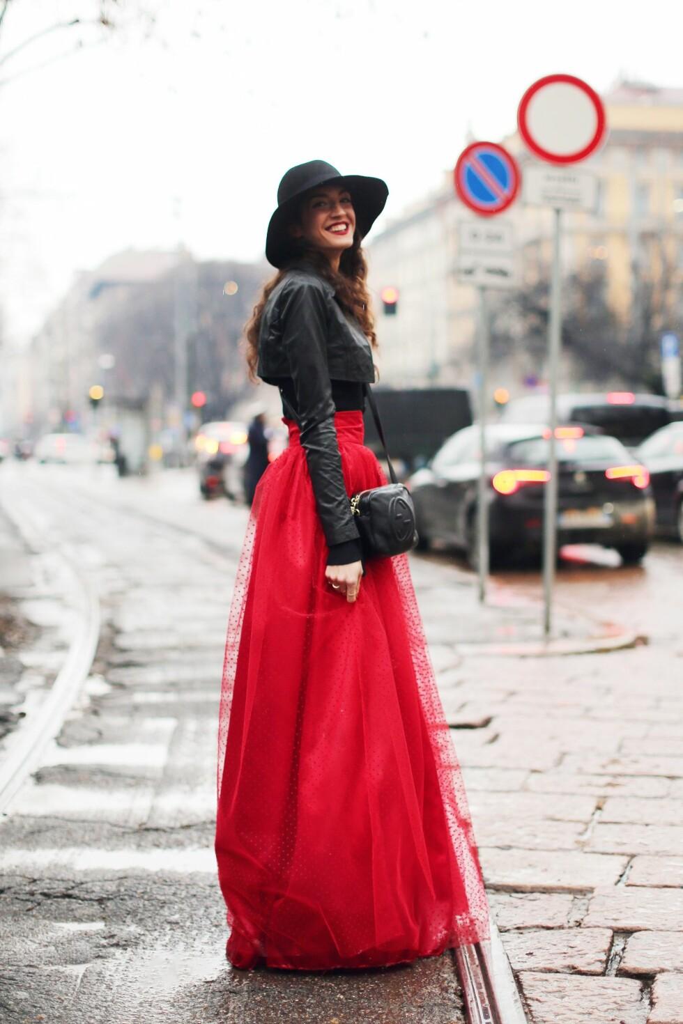 VEKK OPPSIKT: Rødt er en oppsiktsvekkende farge i seg selv, men det trenger ikke bety at du må kle deg diskret og forsiktig når du bruker fargen. Et statementplagg som et langt tyllskjørt i kombinasjon med en nett skinnjakke gir en oppdatert look verdig en fashionista. Foto: All Over