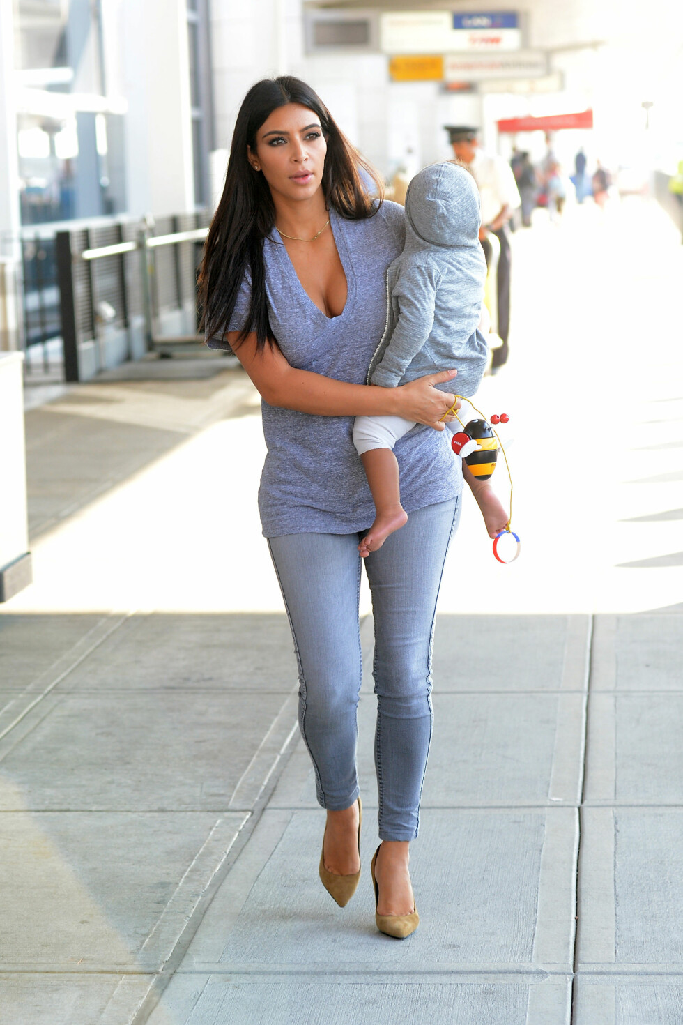 HALVDYP V-UTRINGNING: Vanligvis går Kim Kardashian for lange v-skjæringer på topper og kjoler, men her er hun i kledd i en t-skjorte med halvdyp skjæring - noe som kler store pupper utmerket. Foto: Elder Ordonez/INFphoto.com/ All