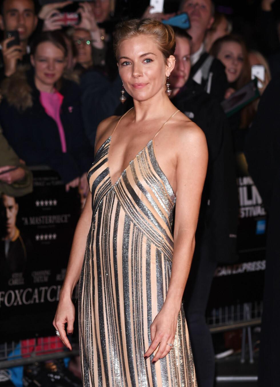AKKURAT PASSE SEXY: Skuespiller Sienna Miller ser chic og leegant ut i denne glitrende kjolen med v-hals - den er akkurat så dyp at den ikke blir tacky. Foto: REX/David Fisher/All Over Press