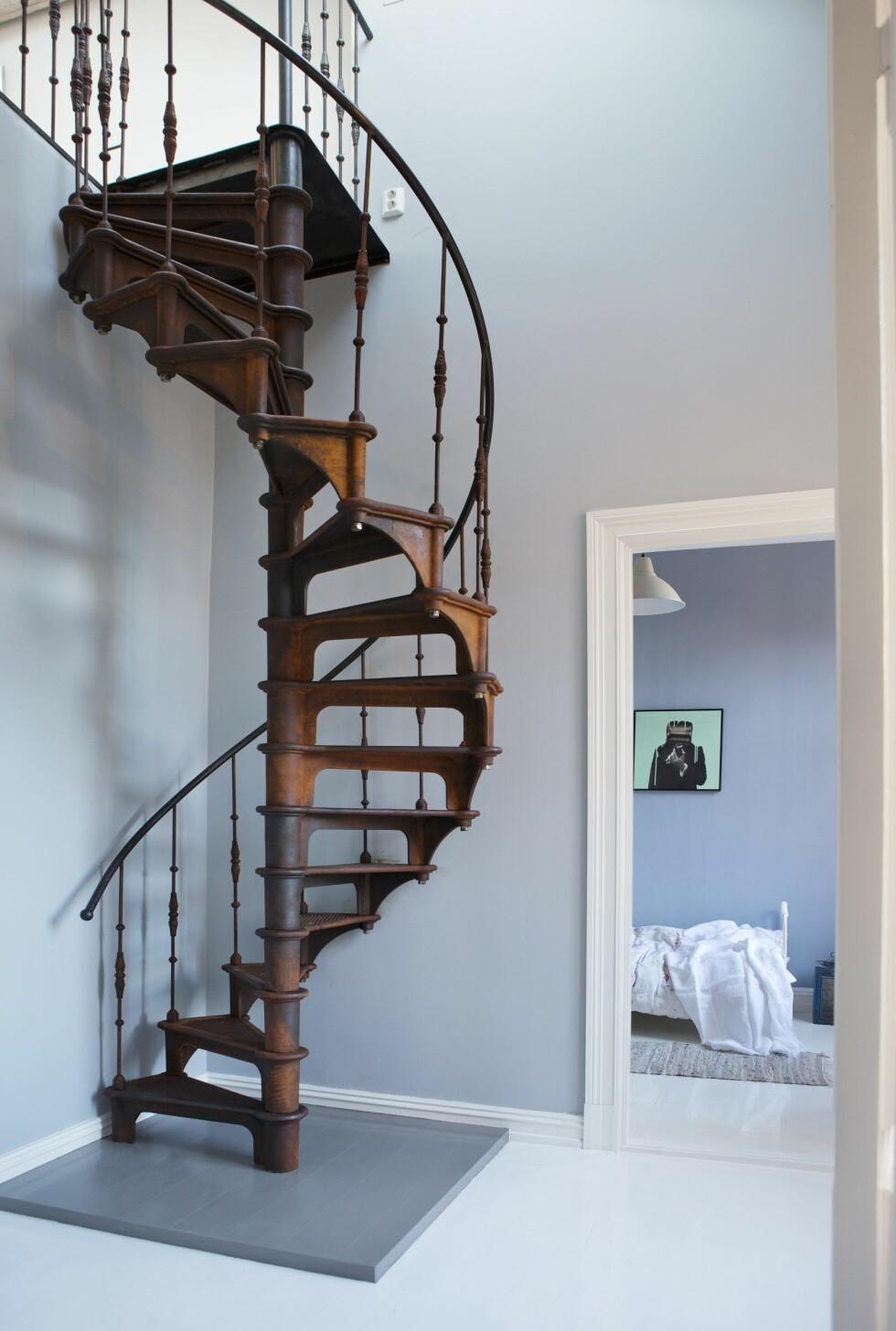 FANTASTISK TRAPP: Da paret kjøpte loftet for å innlemme det i leiligheten, trengte de en trapp. De importerte en fantastisk kopi av en industritrapp fra 1880-tallet, fra Frankrike. Deretter lot de den ligge ute i vær og vind i et par måneder for å få den røffe patineringen, før den ble behandlet med Owatrol. Rommet innenfor brukte Edvard Munch trolig som utgangspunkt til maleriet «Sykt barn». Et bilde malt av Ørjan pryder veggen. Foto: Yvonne Wilhelmsen