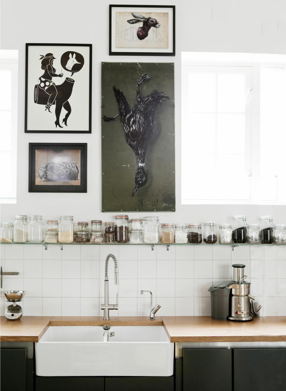 TIL KRYDDER: På den lange glasshyllen over kjøkkenbordet står patentglass i forskjellige størrelser fylt med alt fra krydder til kaffe og gryn. En både praktisk og dekorativ løsning. Foto: Pernille Kaalund/House of Pictures