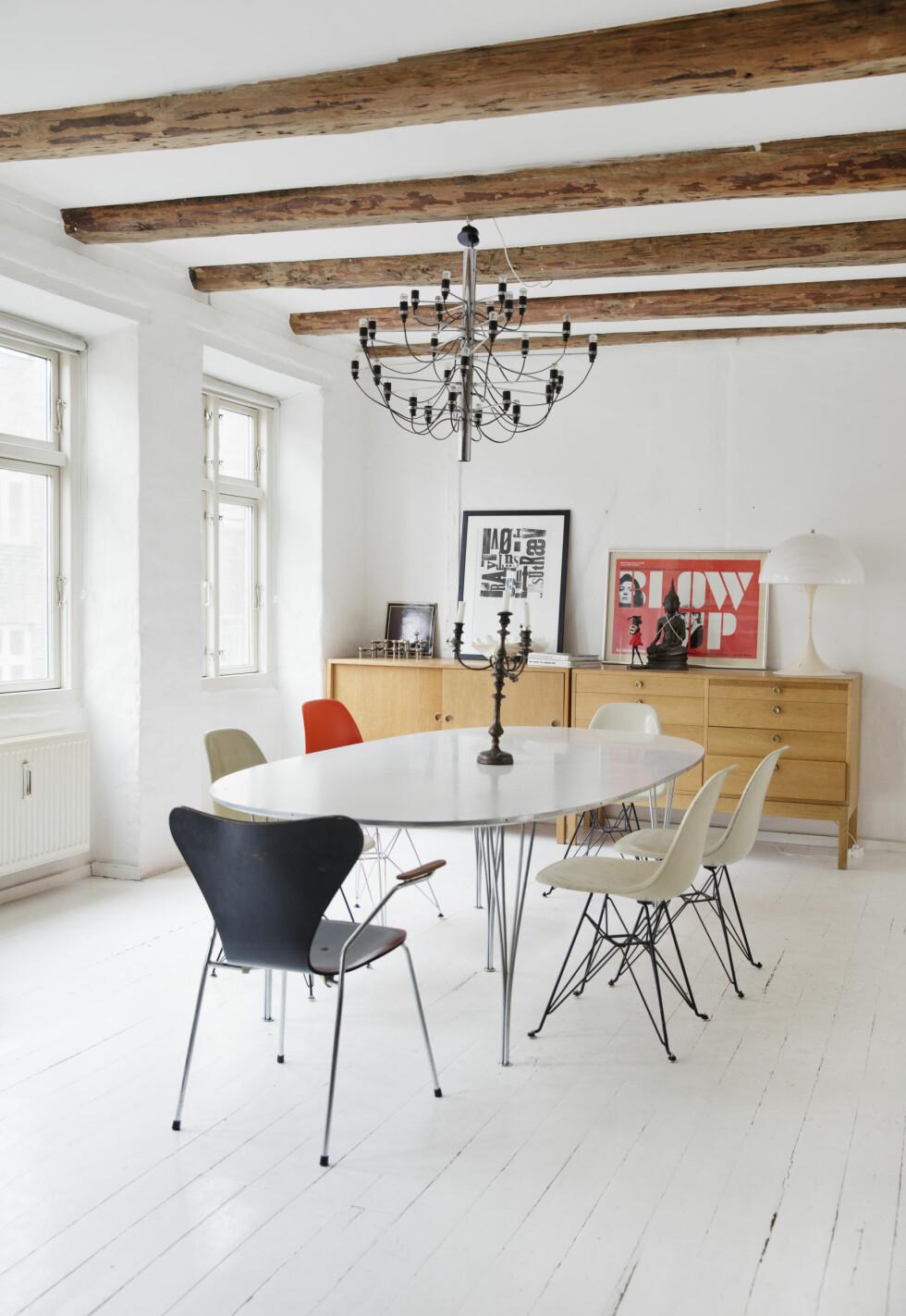 <strong>HERLIG MED GJESTER:</strong> Rundt Piet Heins ellipsebord står Eames- og Arne Jacobsenstoler i forskjellige farger. Stuen er nennsomt innredet. Foto: Yvonne Wilhelmsen
