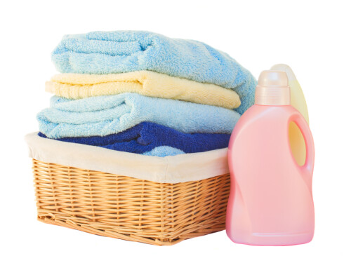 Clothes with detergent  in basket isolated on white background Foto: Fotolia