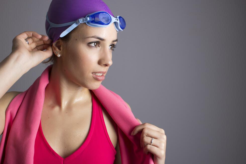 BADEHETTE: For å beskytte deg mot grønnskjær i håret når du tilbringer mye tid i bassenget, er badehette det aller beste valget. Frisørene anbefaler å skylle håret i rent vann og ta i balsam eller hårkur før du tar på badehetta. Kanskje ikke noe for alle, men smart om du vil unngå grønnskjær. Foto: pepa65 - Fotolia