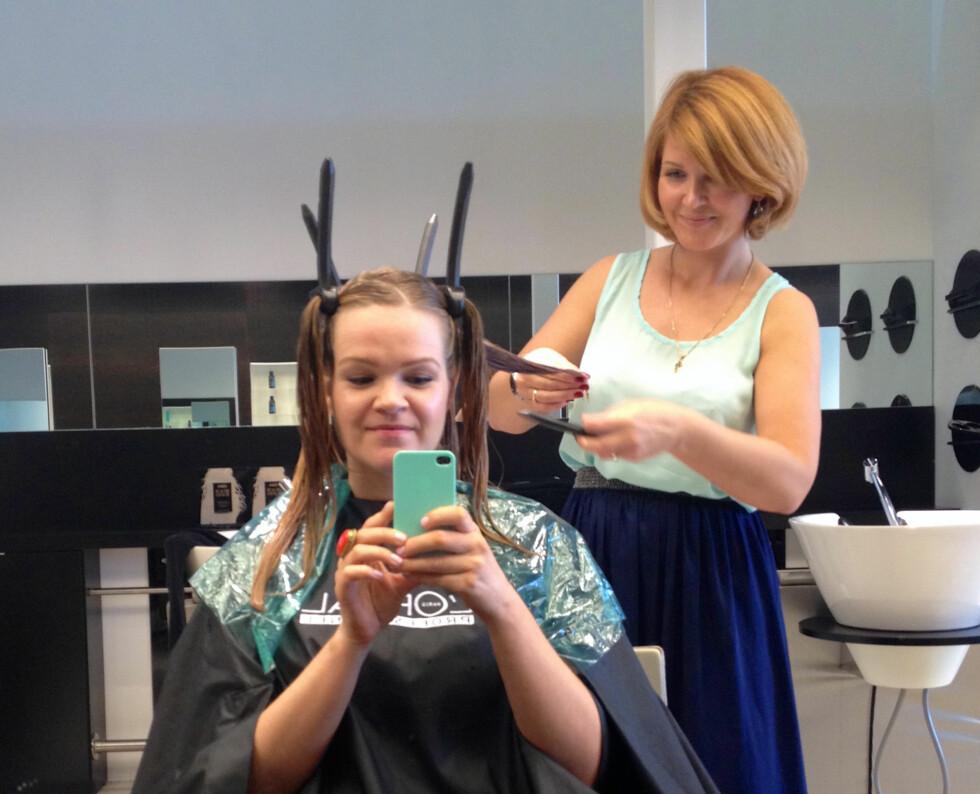 PROSESSEN: Ja, man ser litt latterlig ut mens det pågår. Her ruller Jekaterina Beresneva, opplæringskonsulent i L'Oréal, håret mitt opp på papiljottene.  Foto: Aina Kristiansen