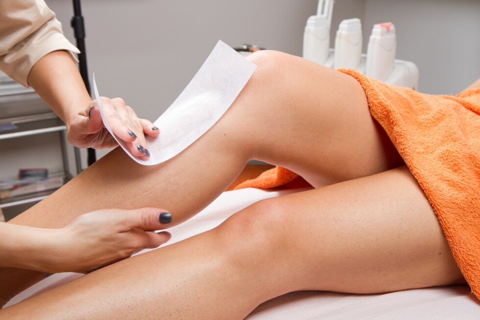 Beautician waxing a woman's leg applying a strip of material over the hot wax to remove the hairs Foto: Lsantilli - Fotolia