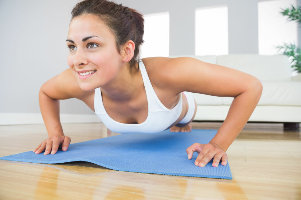 Young fit woman doing press ups on an exercise mat in her living room Foto: WavebreakMediaMicro - Fotolia