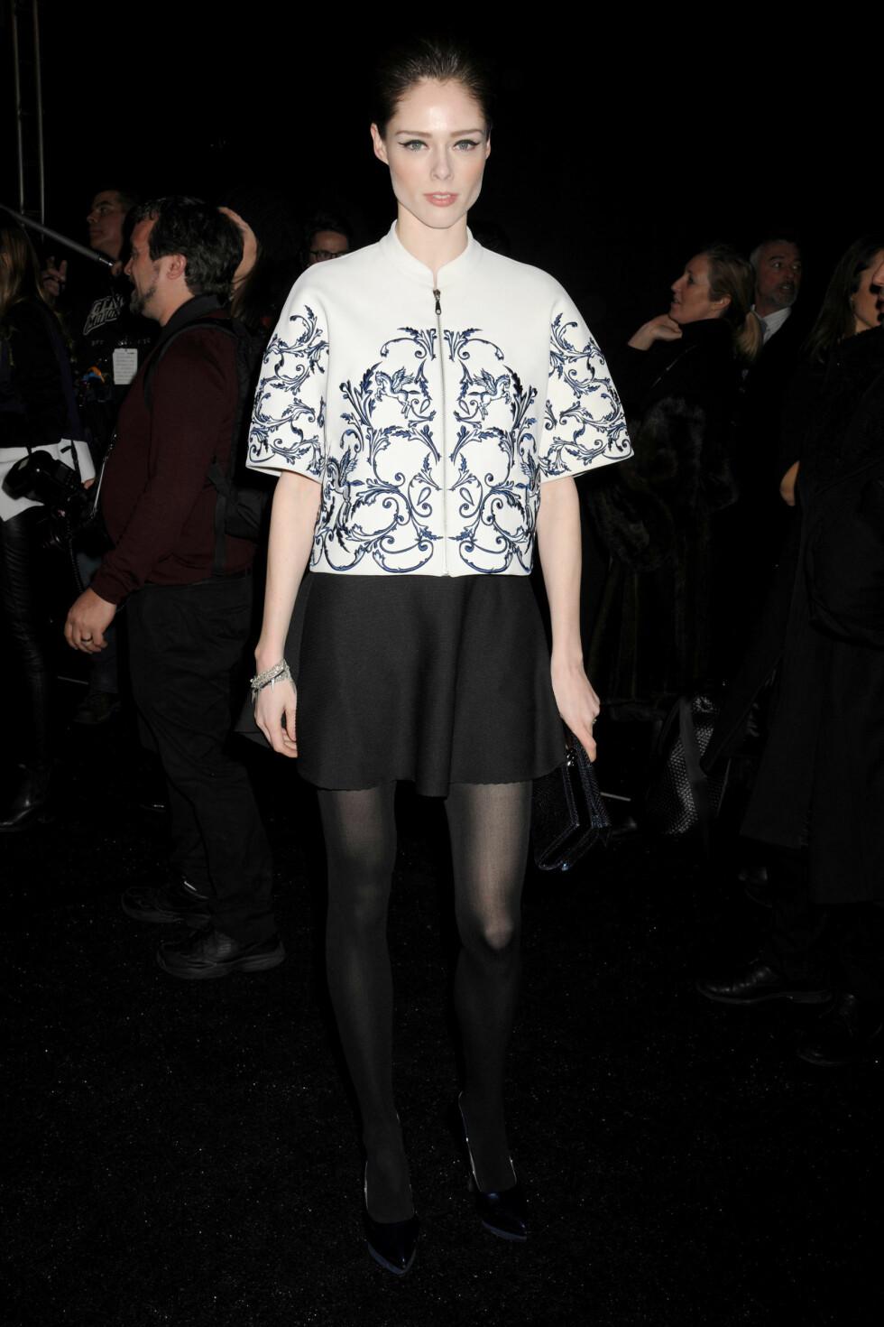 Den kanadiske supermodellen Coco Rocha iført et sort skjørt og en hvit bluse med blått mønster.  Foto: All Over Press