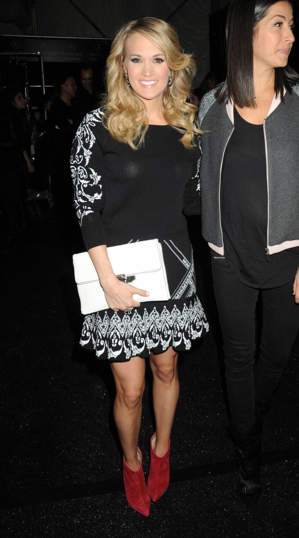 Den amerikanske popartisten Carrie Underwood hadde på seg en sort kjole med hvite detaljer og et par knallrøde ankelstøvletter.  Foto: All Over Press