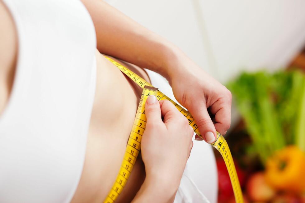 MÅLEBÅND: Et målebånd kan ofte være en bedre måte å finne ut hvor mye mindre fett du har rundt midjen.  Foto: Kzenon - Fotolia