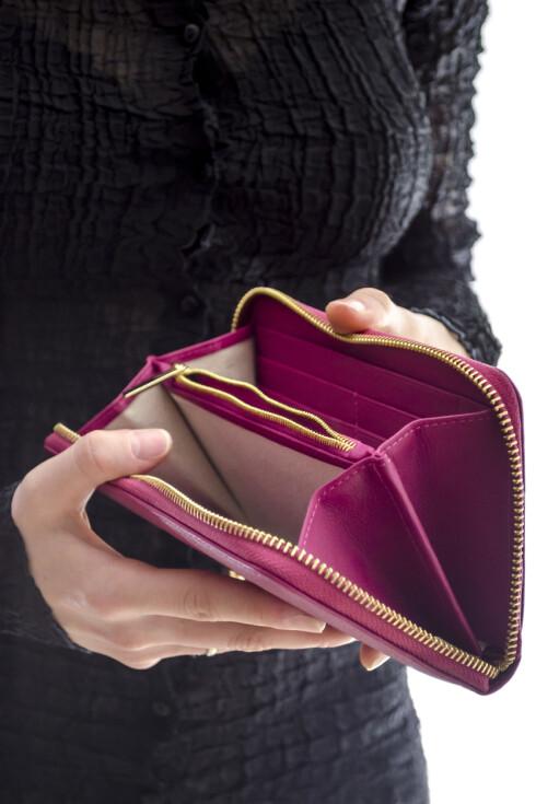 Woman in a black dress holding an empty wallet. Foto: Gajus - Fotolia