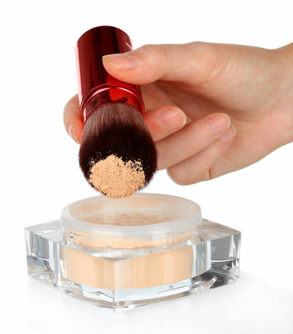 Brush for make-up with powder in hand, isolated on white Foto: Africa Studio - Fotolia