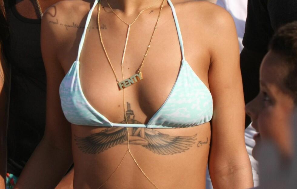 STORE ELLER SMÅ PUPPER - HVA SKAL DU VELGE?: Rihanna går for en enkel trekantbikinitopp som hun styler med et lass av kule gullsmykker. Perfekt triks hvis du vil ha litt større volum på bysten... Foto: All Over Press