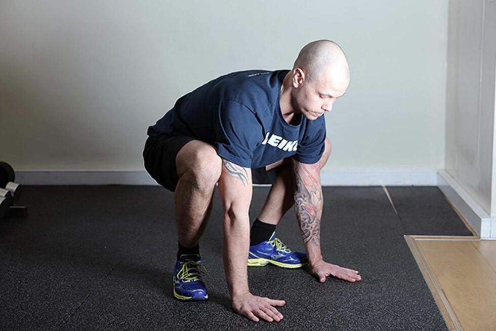 Start sittende på huk med hendene i gulvet. Foto: Øyvind Heia