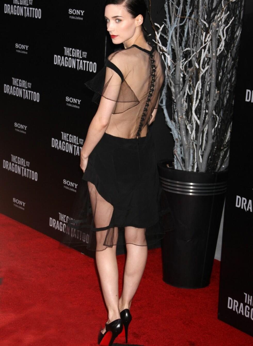 Under premieren i New York, valgte hun en kort, sort kjole med rygg, ermer og deler av skjørtet i tynn chiffon, som viser hud på en delikat måte. Håret er satt opp i en stram sideskill, leppene er røde og hun bruker svarte lakkpumps.  Foto: All Over Press