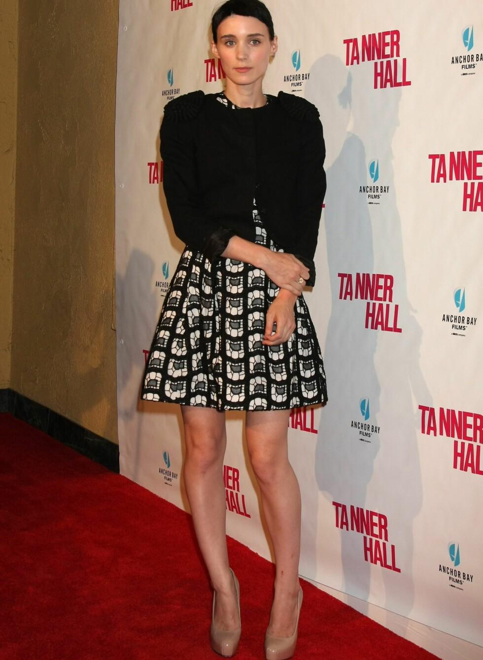 På premiere av Tanner Hall, i Los Angeles, iført en mønstret 60-tallskjole med vidt skjørt, sort cardigan og nude pumps. Foto: All Over Press