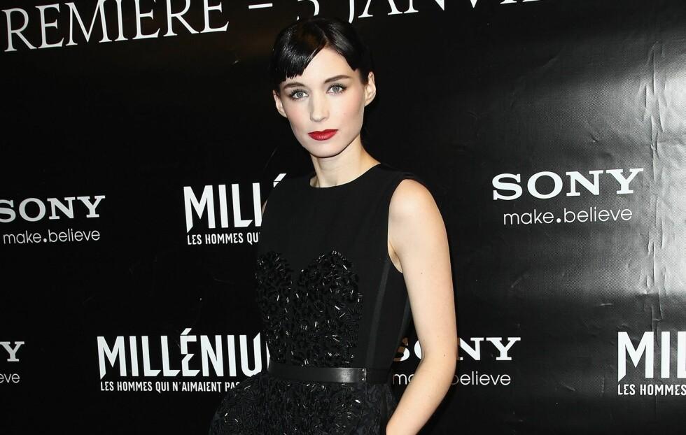 MOTESNAKKIS: På premieren i Paris, iført en kort, sort 60-tallskjole med blomsterdetajer og strass. De røde leppene og sorte sandalene er med på å gjøre antrekket enkelt, men elegant.  Foto: All Over Press