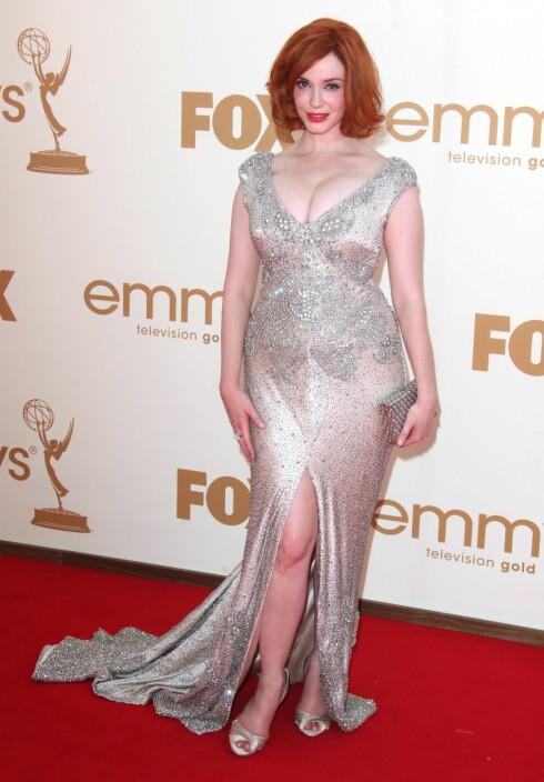 SPLITT: Christina Hendricks i sølvfarget kjole med dyp skjæring og splitt foran. Se ALLE Emmy-kjolene på KK.no's motetjeneste Trendtoppen. Foto: All Over Press