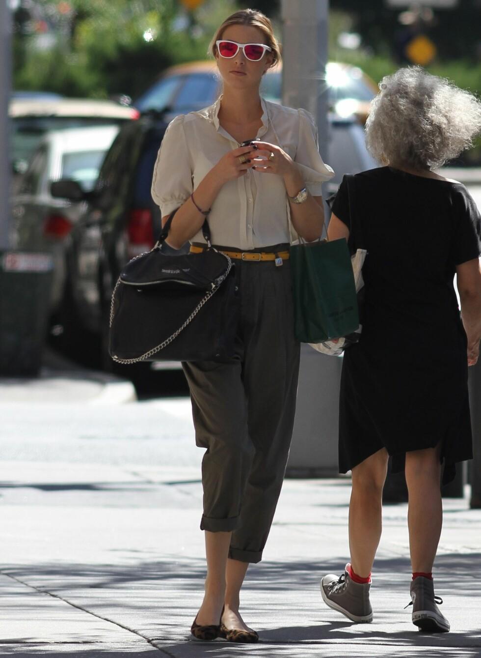 Whitney Port tusler rundt i New York i moteriktig hvit bluse, retrobukser, leopardmønstrede ballerinasko og hvite solbriller. Foto: All Over Press