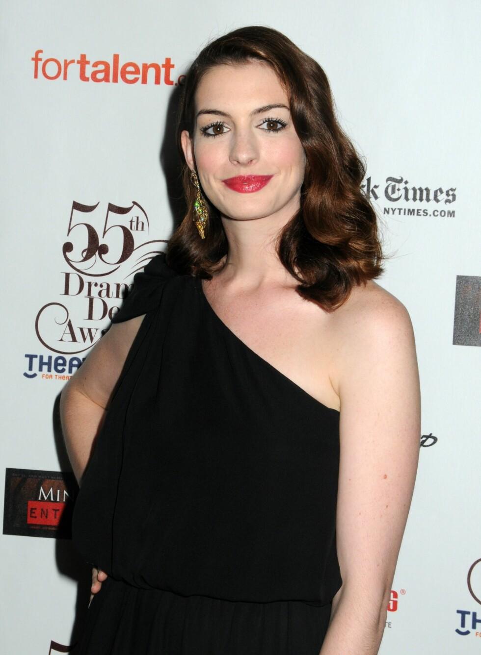 Anne Hathaway ser ser ikke ut til å ha tilbragt mange timene på solsenga denne sommeren heller. Hun er en av stjernene som har like delikat og blek hud året rundt.  Foto: All Over Press
