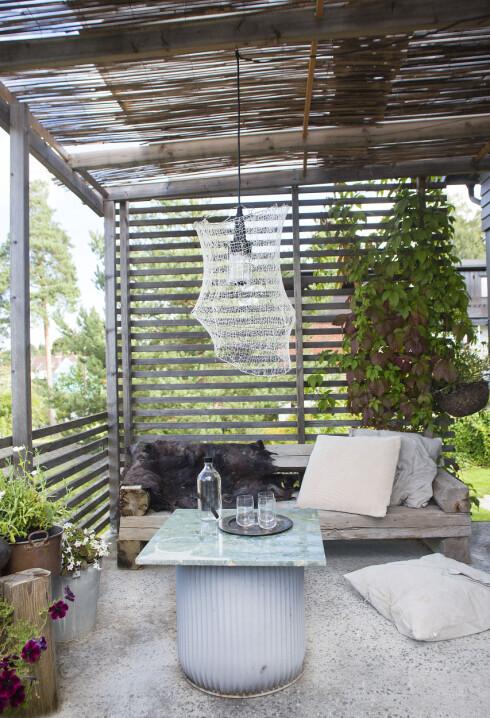 Tips! Et tak av kanalplast med bambusrull under siler lyset så fint over uteplassen.Lampen ute har Marianne laget, hun selger dem på egen nettside. De er strikket i tynt silkegarn, som gir en transparent følelse. Bordet er satt sammen av en blomstertønne og en grønn marmorplate som lå på kjøkkenet da de overtok huset. Putene fra Vølt. Foto: Filippa Tredal